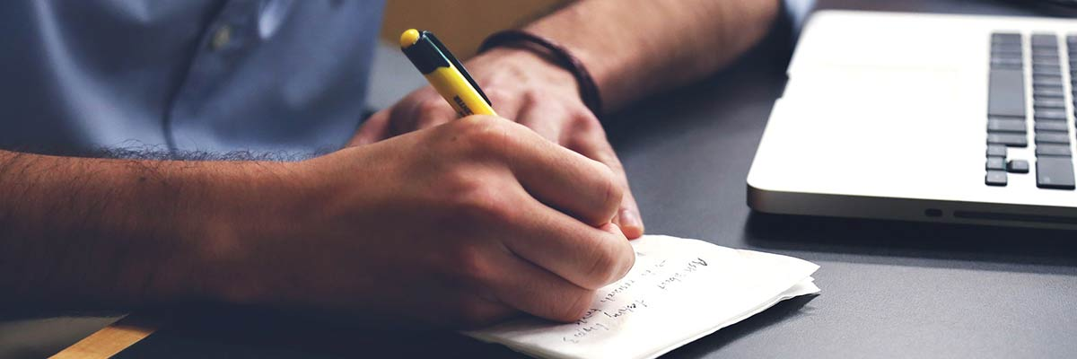 Man med block, penna och dator som förbereder sig inför en intervju med TNG