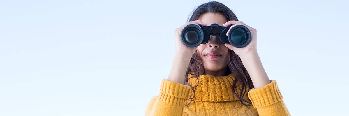 Kvinnlig arbetsgivare håller i kikare som symbol för sökandet efter talanger i rekrytering