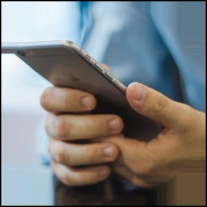 Jobbsökare med mobiltelefon som läser på om arbetsgivaren inför en arbetsintervju
