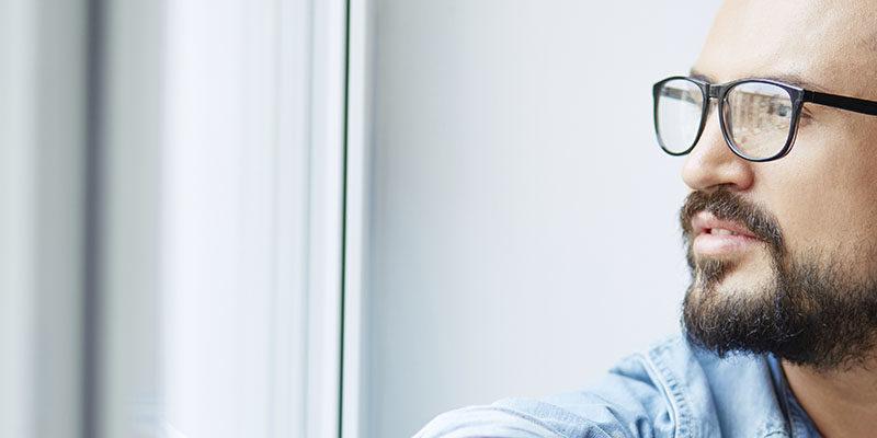 Manlig introvert säljare blickar ut genom fönster