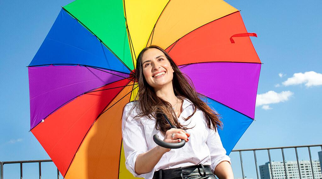 fordomsfri-rekrytering-glad-kvinna-paraply-fargglad himmel